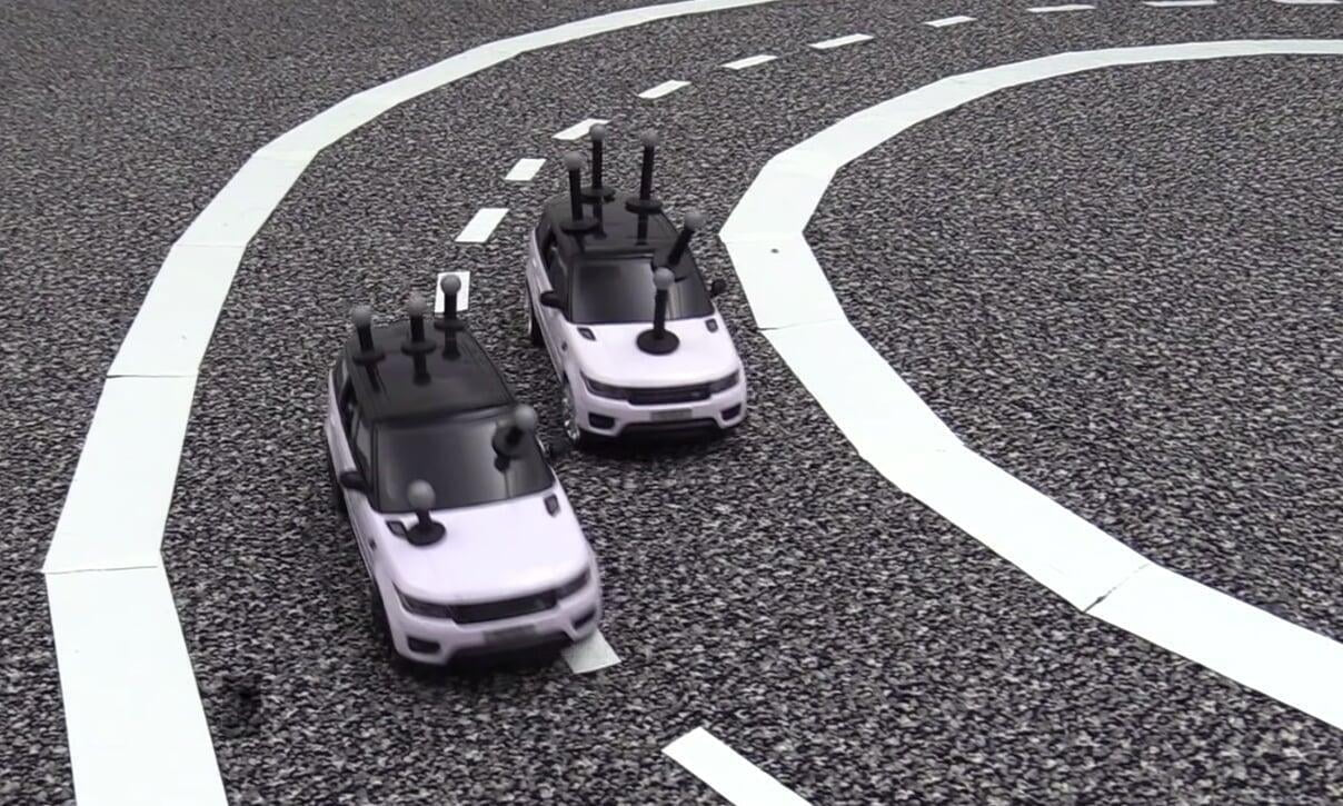two model driverless cars on a black and white track