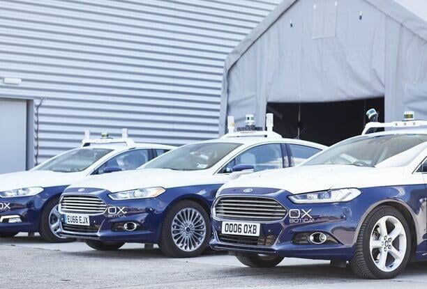 Three blue Ford Mondeo car outside a warehouse