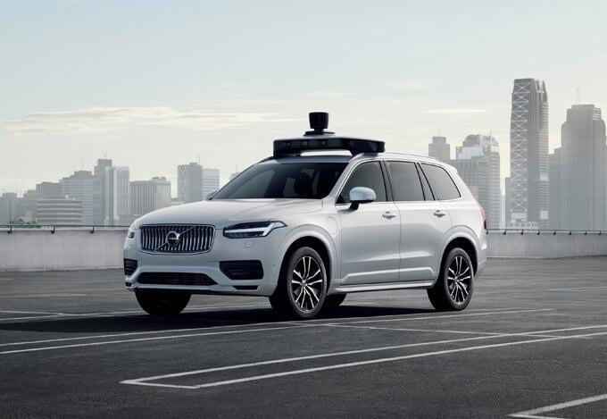 White, self driving Volvo XC90 SUV with city skyline in the background