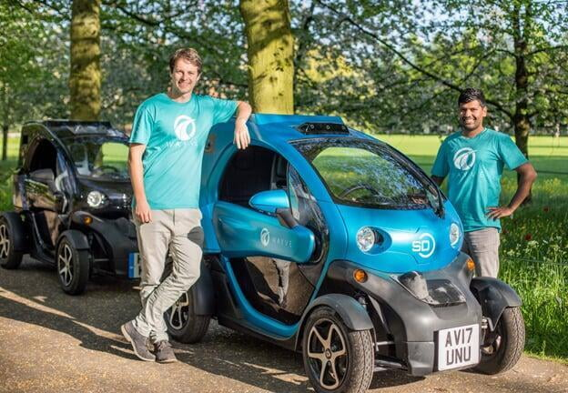 Two men in green shirts with an electric car in a park