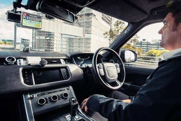 Interior of an autonomous land rover with a driver whose hands aren't on the steering wheel